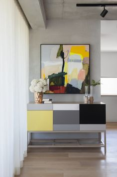 contemporary colorful furniture | large abstract painting in hallway | concrete walls | residential interior design ideas