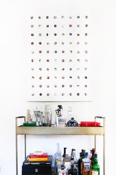 Home bar fully stocked underneath oversized artwork