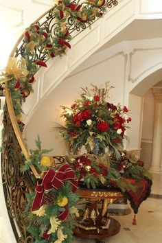 Beautiful choice of holiday materials for this garland, table, and flower arrangement. The wrought iron bannister is stunning.