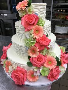 Gorgeous river of flowers on your wedding cake. Stunning coral roses, peach mini gerberas and touches of antique hydrangea.  Contact Marion at Bayview Florist Wedding Studio in Sayville, NY. Maz851@aol.com