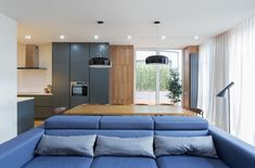 A bright blue sofa adds a playful splash of color to the living room and brings out the bluish hues blended into the gray cabinetry in the background.