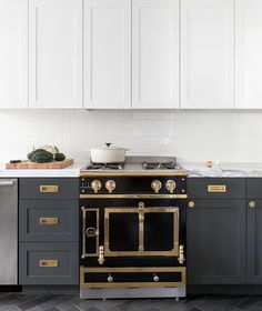 A La Cornue Range Le Chateau range is placed on gray herringbone floor tiles between gray shaker cabinets complemented with vintage brass inset hardware and a gray and white marble countertop fixed against white subway backsplash tiles beneath white shaker upper cabinets concealing a vent hood.