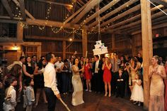 The bride and groom with their wedding cake pinata. Michigan outdoor barn weddings.