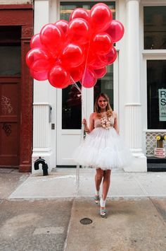 I want to hold of bunch of red balloons, wear a puffy ballet dress with heals and then just run around the city. I do.