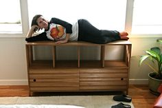 A solid oak Eames-inspired cabinet with sliding door fronts, modeled by the happy client.