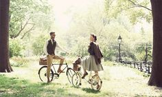 The wind ruffles her skirt as the boy shifts his bicycle, two lovers enjoying the breeze and lovely garden.