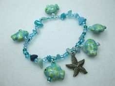 A FUN BRACELET WITH A NAUTICAL THEME.  BLUE AND YELLOW FISH, TURQUOISE AND BLUE SEED BEADS AND A SILVER STARFISH CHARM ARE COMBINED TO MAKE A CUTE, STRETCH BRACELET.  THIS ...