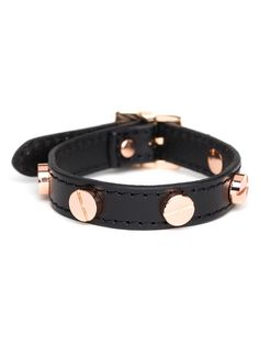 This chic bracelet offers a witty take on the classic leather bracelet. The subversive accent? Glam gold hardware in the shape of screws.