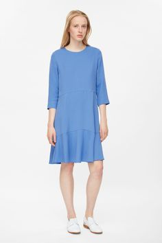 This dress is made from circle-cut panels of fluid fabric for a subtle flared shape. A loose fit, it has a simple round neckline, 3/4 sleeves and in-seam pockets. It is completed with a hidden zip fastening along the back.