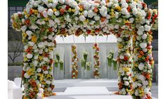 """""""This was a client who wanted to create two events out of the same structure.  So we left the white structure for the wedding, then flipped it over and added oranges and yellows to give it a pop of color. That's what I love about flowers: everyone can have a different floral experience, even at the same event."""""""