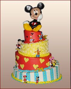 """This round four-tier topsy turvyMickey Mouse themed cake would """"WOW"""" the crowd at your child's next birthday party. The baby blue buttercreambottom tier iselegantly furnished withwhite verticalfondant stripes. It is trimmedwithyellow and baby bluebuttercream beading. The base of the next tier isa deep redbuttercream withfondant yellow hearts aroundit.The third tier is garnished with squiggly white piping and can accentuate the fun-filled theme. Palermo's Custom Cakes."""