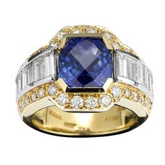 This exceptional sapphire and diamond ring makes a bold statement. Showcasing a sparkling 3.78-carat sapphire at its center, this stunning ring also features approximately 1.80 carats of diamonds, both channel-set emerald cut and round brilliant stones, providing the perfect accent. Set in a dynamic 18K yellow gold