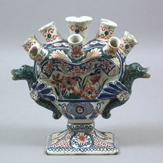 An 18th Century Dutch polychrome Delft two handled tulip vase by Lambertus Van Eenhoorn, painted with flowers, 8ins high with painter's mark to base