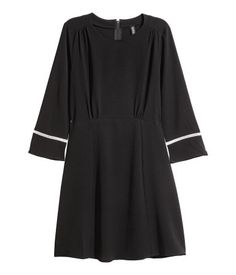 Black. Short dress in woven, crêped fabric with a concealed zip at back. 3/4-length sleeves with hemstitched inset trim at cuffs. Seam at waist and a gently