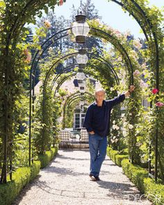 Gruosi, the founder of the jewelry firm De Grisogono, under the rose arbor in his front garden.