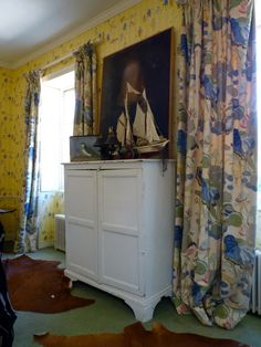 Floral curtains in blue/green/beige.  Yellow walls floral.   Ship model.