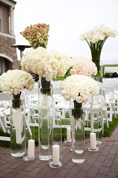 Arrange white flowers in tall glass vases for modern ceremony decor that can be reused for the reception
