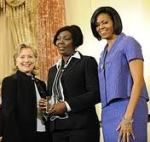 Solange (Sonia) Pierre being presented with an award by Hillary Clinton and Michelle Obama.