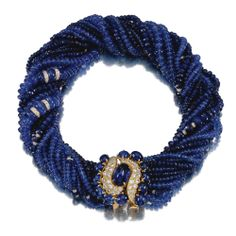 SAPPHIRE AND DIAMOND TORSADE Composed of eighteen rows of faceted and polished sapphire beads, interspersed at intervals with brilliant-cut diamond rondelles, to a clasp of stylised scroll design set with cabochon sapphires and brilliant-cut diamonds, length approximately 410mm.