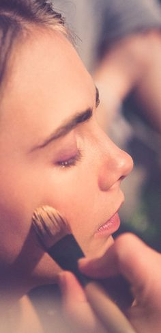 British model Cara Delevingne has her Burberry make-up applied backstage