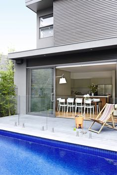 """Full-height glass doors at the rear of the house and the glass pool fence work in tandem to make the area feel larger than it is. Philippe Starck Bubu stool/side **table** from [Space](http://www.spacefurniture.com.au/