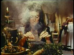 A Witch practicing Herbal Magick. She is pinching up herbs to put in her cauldron. The herbs are called for in the spell she is working.