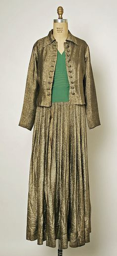 Circa 1935 Evening suit by Robert Piguet: metallic gold suit dress, green shirt top, jacket, and skirt pleats.