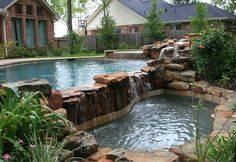 This is a lovely pool with a very unique feature. This is pool has a negative edge that spills into a small alcove pool that is a lovely private space tucked away in a garden. In the background of this image the stacked stone spa spill way is visible.