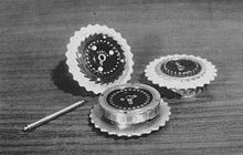 Three Enigma rotors and the shaft on which they are placed when in use. https://sites.google.com/site/warrenbellauthor/