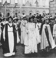 British prison garb is marked all over with a three-stroke arrow to denote a prisoner. The Broad Arrow became a badge of honor worn by suffragists who'd endured imprisonment. Here, the Pankhursts lead a group of WSPU marchers, each bearing a Broad Arrow on her parade staff.
