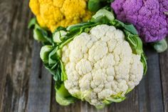 Yellow, purple and white cauliflower heads on a wooden table