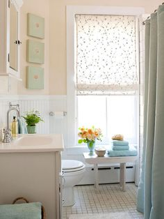 What this bathroom lacks in size it makes up for in sweet style, thanks to a handful of decorative touches. A tiny bench tucked under a window holds fresh-cut flowers, decorative soaps, and extra towels. The room?s gentle peach and soft green color palette keeps the narrow space feeling open and inviting.