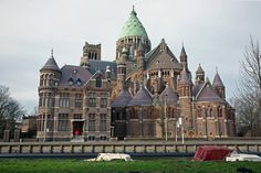 I adore this building!  It's the Kathedraal St. Bavo, Leidsevaart, Haarlem, or St. Bavo Cathedral (Catholic) in Haarlem, Netherlands, built in 1898.  The clump of rounded portions with turrets next to a straight line section, tons of windows, and the nice green (I presume copper) large tower are just captivating!