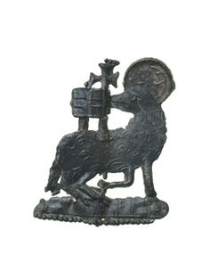 Devotional badge in the form of the Agnus Dei (Lamb of God). The head is surrounded by a halo. The Lamb looks backwards towards a cross-staff bearing a banner with a cross and holds the staff with one of its front feet, which is held up. This was probably not a pilgrim souvenir from a particular shrine but is more likely to have been worn as an aid to devotion. 14th-15th century | Museum of London