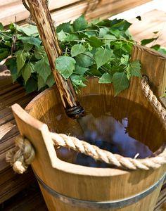Wooden sauna pail + birch whisk used in sauna.