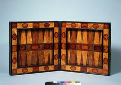 This backgammon board of amber is made in Königsberg in ca. 1608-1647. A comparison with similar gamesboards suggests that originally amber was originally inlaid on the external as well as the internal surfaces; the outer decoration is now lost. Gamesboards such as this were produced in Königsberg (then in Prussia), as well as in other Baltic cities. The myth of Phaeton depicted here in one of the small reliefs is eminently suitable for an amber piece.