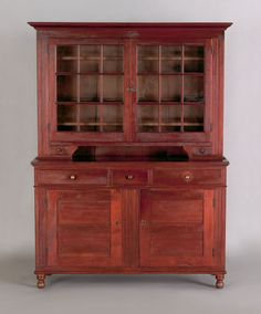 """Realized Price: $11,700 Pennsylvania walnut two part dutch cupboard, ca. 1825, the molded cornice over two glazed doors flanked by molded pilasters and chamfered corners, above two candle drawers, resting on a lower section with three drawers and two recessed panel cupboard doors supported by turned feet, 83 1/2"""" h., 59 3/4"""" w. RICHARD MACHMER COLLECTION 2008"""