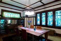 contemporary dining room, prairie style stained glass, contemporary chandelier, molded plywood chairs, built in china cabinet, white walls with dark wood trim