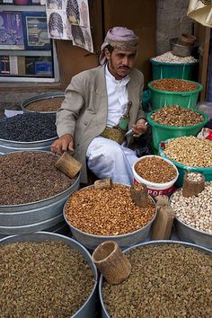 A raisin and nut seller waits for customers in the old city, Sana'a Yemen.