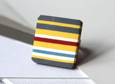 Ring with red grey white yellow and blue stripes by zsbekefi