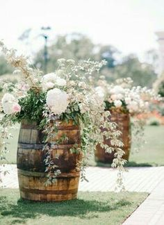 Barrels full of flowers to flank the country driveway.