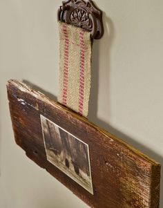 Sepia-toned photo and old piece of wood, hung with upholstery strap and cabinet pull -