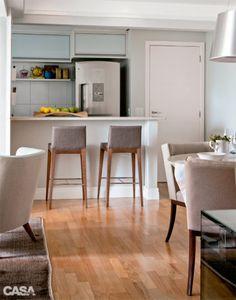 Aberta para a sala, a cozinha tem balcão de alvenaria e banquetas do Empório Vermeil.
