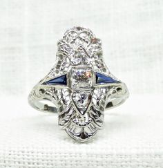 Gorgeous dinner ring from the Art Deco era in 18 karat white gold, set with diamonds and blue sapphires. The ring is a classic dinner ring style, with an oblong setting of elaborate openwork filigree set north to south with three sparkling diamonds. The center diamond is .15 carats, and is G/H in color. The two side diamonds are .06 carats each, and are also G/H in color. Set on the rings shoulders are two elongated, triangular blue sapphires approximately .10 carats each, bringing ...