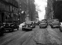 La rue Peel dans l'ouest de Montréal au printemps 1938. Quelques automobiles circulent péniblement dans la neige fondante. Sur le côté droit de la rue : la boutique «Canadian Handicraft Guild», située au 2019 de la rue Peel ainsi que «Rivay Dress Shop».