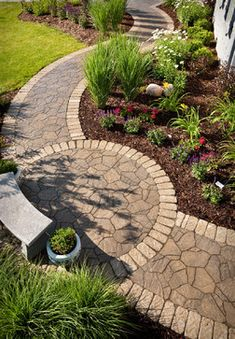 #Curved #Stone #Pathway intersects a #Round #Patio with stone bench..