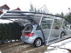 A transparent glass cover, whose shape is defined by the steel beams in blue and gray. A forward-looking, ergonomic and aerodynamic garage design. Design Garage, Carport Designs, Pergola Designs, Door Design, House Design, Pergola Carport, Pergola With Roof, Gazebo, Outdoor Pergola