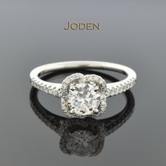 A simple twist on a modern halo is what makes this diamond engagement ring so unique. The scalloped halo surrounds one round brilliant cut diamond that has a weight of .64 carat. This diamond has a color grade of G-H and a clarity grade of VS(1-2). The 40 round brilliant cut accent diamonds have a weight of .28 carat total weight with an average color grade of G-H and an average clarity grade of VS(2)-SI(1).