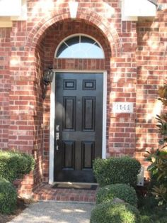 recessed front door.  Brick lines the recessed area, narrow trim and black door