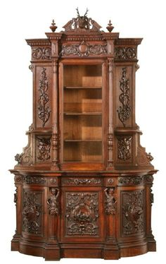 """Oversized 19th century carved oak huntboard features a fully carved deer head on the pediment and intricate relief carvings throughout. The demi-lune base cabinet features a pair of curved door panels with lion masks at the center of relief carved medallions, and a central door with relief carvings of playful squirrels, all interspaced by maiden term figures.  Attributed to American master carver Alexander Roux. 120""""h x 75""""w x 30""""d."""
